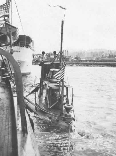 An early 63-foot A-class submarine, likely USS Grampus (SS-4) or Pike (SS-6) on the Willapa River, at Raymond, Washington, circa 1912. The stern of the USS Chattanooga can be seen in front of the sub. Photo provided by Steve Hubbard of the Pacific County Historical Society, Washington State via Pigboats http://pigboats.com/subs/a-boats.html