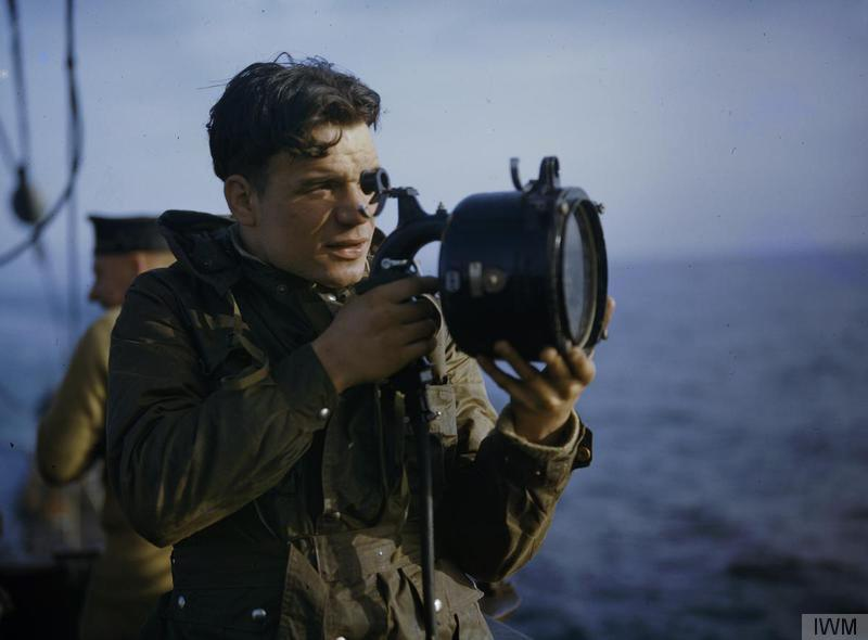 A signaller with an Aldis lamp on board HMS TRIBUNE.