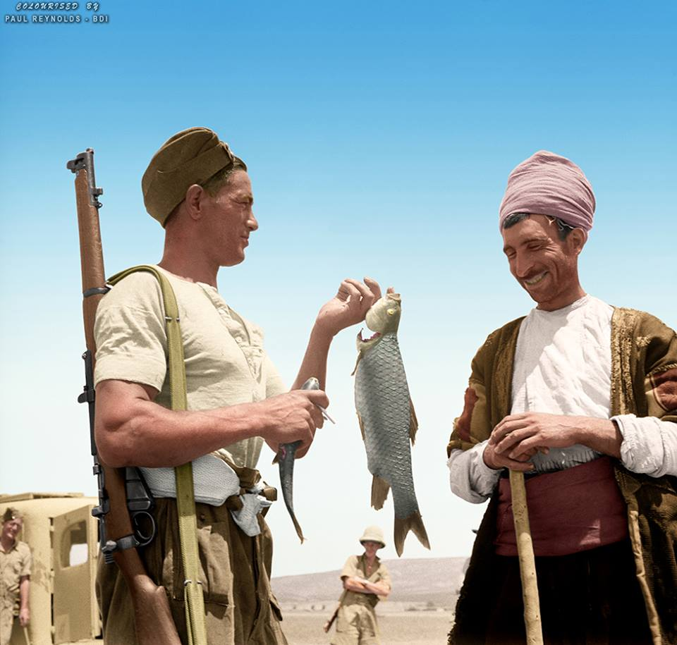 'Been fishing...Got fish' A New Zealand soldier J Thompson (Taihape), shows his catch to a Kurdish local after fishing with rifles and hand grenades on the Syrian Turkish border during World War II, 9th July 1942. Photograph taken by M D Elias. Colourised by Paul Reynolds.