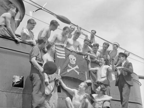 crew of the TRIBUNE pose around their Jolly Roger 6 june 1943 portsmouth note the dagger for the corsican commando landings