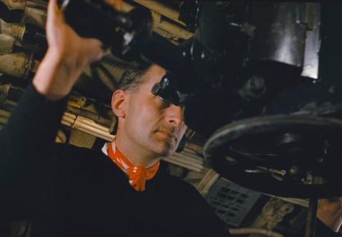 Lieutenant Commander G D A Gregory at the periscope of HMS TRIBUNE
