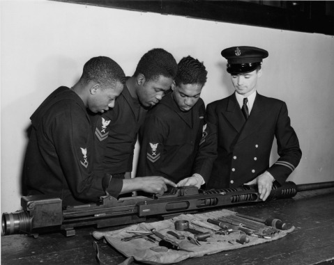 three gunner's mates assemble and study a 20 mm gun, the type which they man aboard the USS MASON (DE 529)