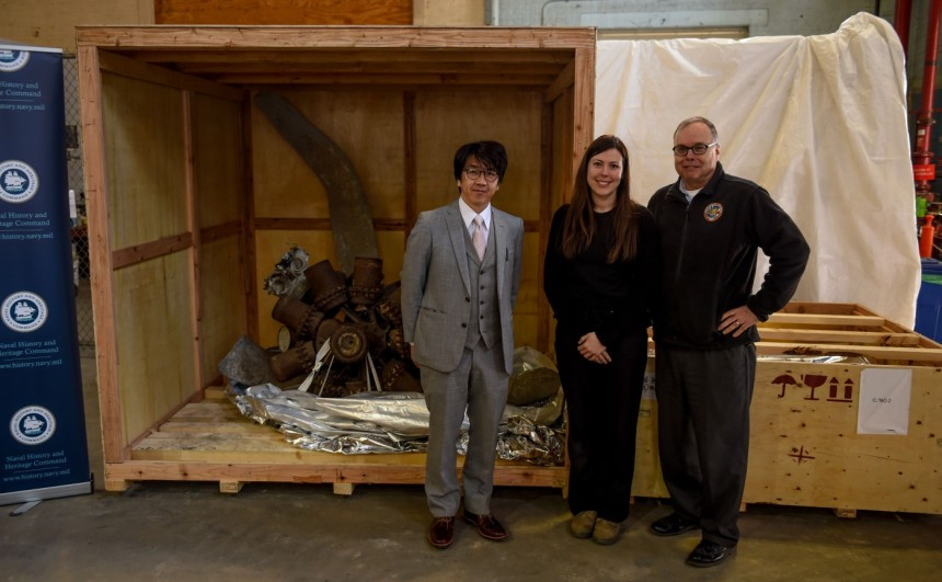 Director of Naval History and Heritage Command (NHHC) Sam Cox (right), Kate Morrand (middle), Senior Conservator & Laboratory Manager of NHHC's Underwater Archaeology Branch, and Yoshiro Kishida (left), a representative from Saiki, Japan, pose in front of the remains of a World War II F4U Corsair fighter-bomber during a presentation in which NHHC accepted the artifact, March 22. (U.S. Navy photo by Mass Communication Specialist 2nd Class Eric Lockwood/Released)