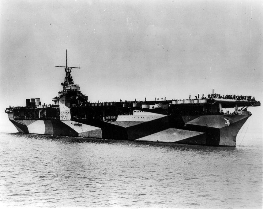 An aerial view of the USS Ranger (CV-4) as she lies at anchor with crewmembers lining her deck. 1944. Naval Aviation Museum Accession Number 1996.488.013.024