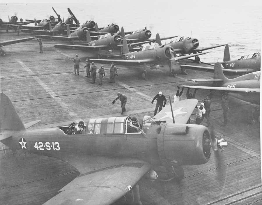 "Flight deck operations, 19 November 1941, showing Vought SB2U ""Vindicators"" of VS-41 and VS-42 getting ready for a patrol flight, and a Grumman F4F-3 ""Wildcat"" of VF-41 (right). Note marking schemes in use on planes, white codes, crew of plane in foreground in cold weather gear. Description: NHC Catalog #: 80-G-391590"
