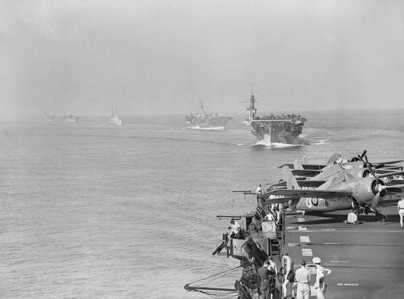 Scene from HMS PURSUER of other assault carriers in the force which took part in the landings in the south of France on the 15 August 1944. Leading are HMS ATTACKER and HMS KHEDIVE. Three Grumman Wildcats can be seen parked on the edge of PURSUER's flight deck. IWM A 25184