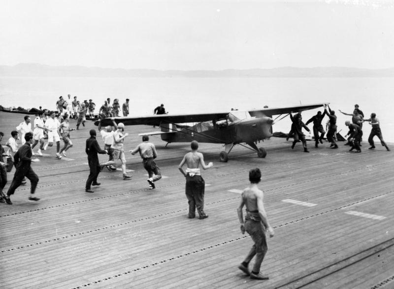 The handling party nearing the Auster as it runs up the flight deck on Khedive, Operation Dracula. IWM A 28833