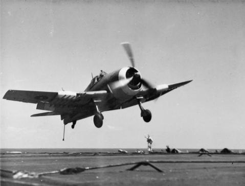 """Too high go round again!"" The Batsman is waving his bat to indicate to the pilot of this Hellcat fighter that he is too high to make a safe landing on Khedive. This shot shows plainly the way the arrester hook hangs down in a position to engage the arrester wires stretched athwartships. A 29038"