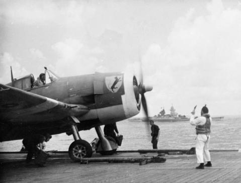 The French battleship RICHELIEU steaming in company as the KHEDIVE's flight deck control officer (wearing Mae West) gives taxiing instructions to a Naval Hellcat pilot when guiding a fighter into position on the catapult. IWM A 29078