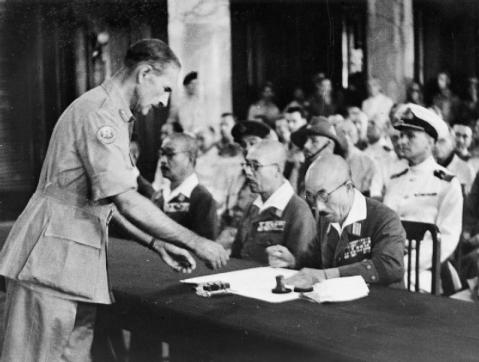 Admiral Mountbatten presides ofter the Surrender ceremony at Singapore. General Itagaki signs the Instrument of Surrender