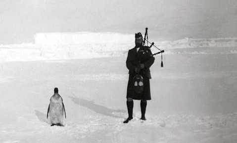 Gilbert Kerr, a member of the Scottish National Antarctic Expedition serenading an Emperor penguin, 1904