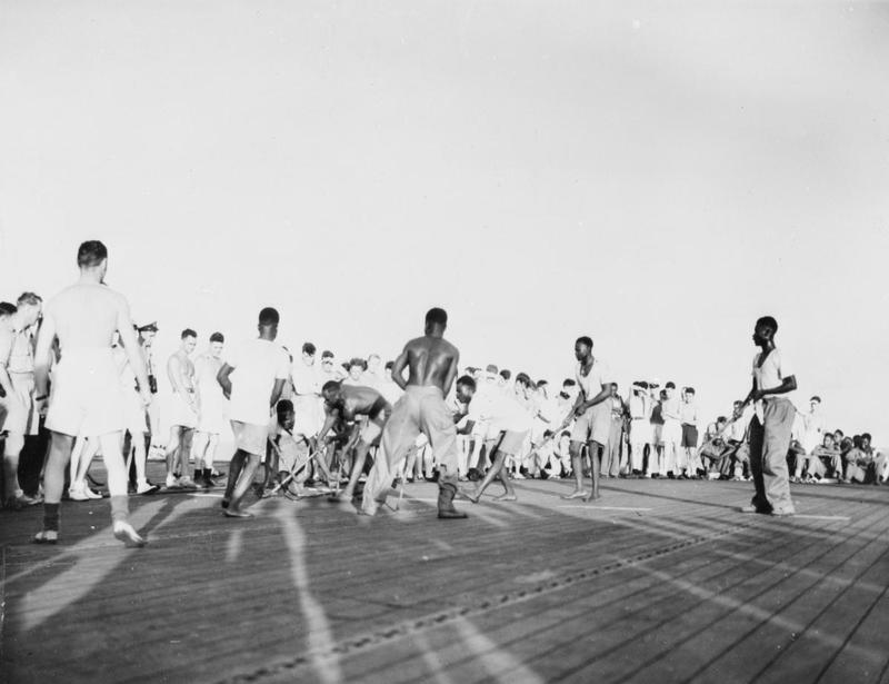 West African troops playing deck hockey with ratings on board HMS Khedive en route to Burma, April 1945.