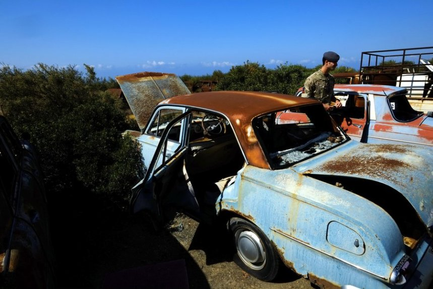 A British soldier walks past abandoned vehicles at the British military base in Episkopi near the southern coastal city of Limassol in the Mediterranean island of Cyprus, on Wednesday, May 25, 2016. The cars were abandoned by Turkish Cypriot owners inside a British military base amid the confusion of a war 42 years ago that cleaved Cyprus along ethnic lines. Now base authorities are hoping to reawaken the interest of owners to reclaim these vehicles before their disposal starts next year. (AP Photo/Petros Karadjias)