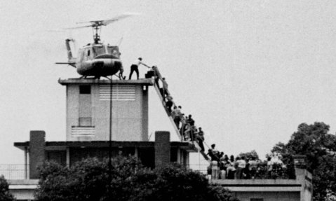 Evacuees are helped aboard an Air America helicopter perched on top of a building in Saigon. Photograph: Hugh van Es/REUTERS