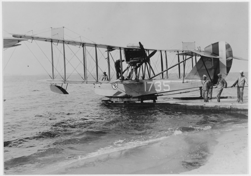 """Curtiss HS-1L seaplane (Bu. no. 1735) of the type flown against U-156, here shown at Naval Air Station Pensacola, Florida Caption: On the ramp at Naval Air Station Pensacola, Florida, circa 1918. Note insignia (patriotic, """"Uncle Sam"""" hat), presumably of Training Squadron Five. Description: Catalog #: NH 44224"""