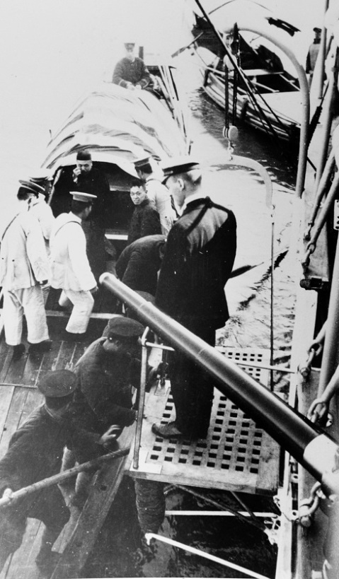 Chinese general visiting Elcano. The commanding officer of Elcano is seen waiting to greet him at the top of the gangway, Ichang, China, circa 1920's. Also note how they have to walk right into the muzzle of the 4-incher when coming aboard-- very subtle. Look up: Gunboat diplomacy. Description: Catalog #: NH 68976