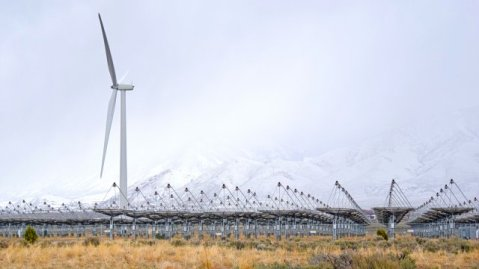 A second wind turbine towers nearly 300 feet above the nearby Stirling solar array at Tooele Army Depot, Utah, March 22, 2016. The $6.5 million wind turbine project is scheduled to be complete later this year and begin generating power. The 1.5 megawatt solar array, consisting of 429 Stirling engine solar dishes spread across 15 acres, is scheduled to be fully operational in 2017. (U.S. Army photo by John Prettyman/released)