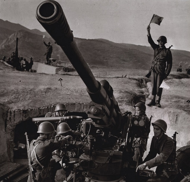 Albanian People`s Army troops man an obsolete M1939 85 mm AAA gun while they carry that country's unique SKS design with their distinctive extra-long gas tube covers. Albania withdrew from the Warsaw Pact in 1968 and after her already dated armament was frozen in time after that. Dig the Chinese style stripper-clip belts (you can see it really good on the signal guy).