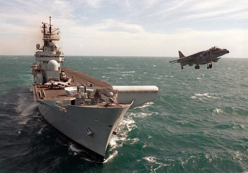 HMS Illustrious, an Invincible-class Britsh Harrier Carrier with a Sea Harrier lifting off her ski jump