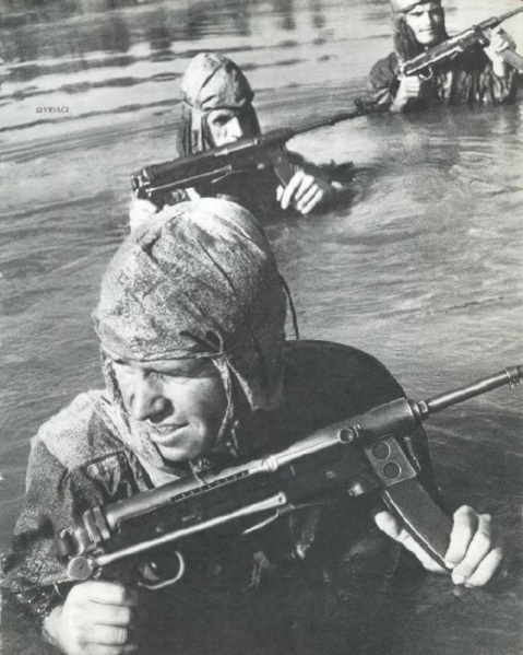 Yugoslav People`s Army soldiers crossing a river M56 Submachine guns. These Yugo-made room brooms were chambered in 7.62×25mm Tokarev and cheaply cloned from the classic German MP40