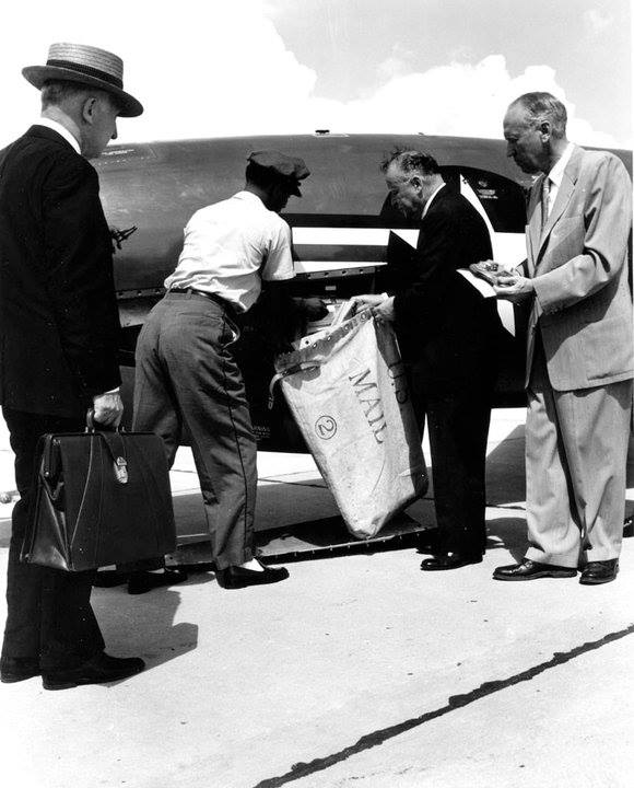 Letter carrier Noble Upperman places first guided missile letters in mailbag as other postal officials look on. Postmaster General Arthur E. Summerfield is to the right of Upperman holding the bag. The Regulus Missile fired from USS Barbero (SS 317) landed at Mayport, Florida. NHHC Photograph Collection, L-File, Weapons.