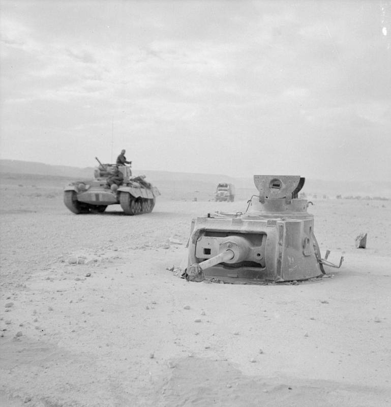 German captured Matilda tank that had been captured and concreted into position to be used as part of the defences of Halfaya Pass, 16 March 1942. A Valentine tank passes by in the background. (IWM E 9320