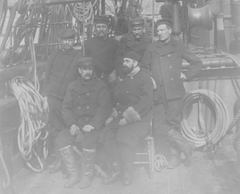 Portrait of Survivors of the Greely Relief Expedition, on board USS THETIS, at Cape Sabine on July 4-8, 1884. Caption: Survivors are shown on board the USS THETIS, at Cape Sabine on July 4-8, 1884. Back row, left to right: Private Francis Long, Sergeant Julius R. Frederick, Private Maurice Connell, Hospital Steward Henry Bierderbick. Seated, left to right: Sergeant David L. Brainard and Lieutenant A.W. Greely. Description: Catalog #: NH 2146