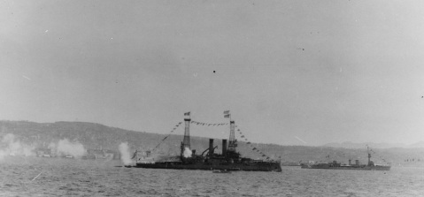 Lemnos (Greek battleship, 1914) Firing a salute to U.S. Navy Admiral Mark L. Bristol, at Smyrna, Turkey, 15 September 1919. Lemnos is flying the U.S. and Greek flags at the foremast peak and the Italian flag at the mainmast peak. A British D-class light cruiser is in the right distance, also with the Italian flag at the mainmast peak. U.S. Naval History and Heritage Command Photograph.