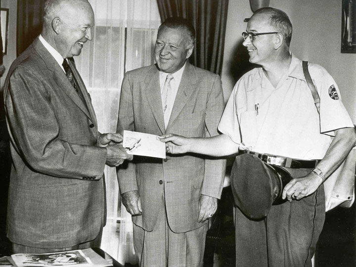 President Eisenhower (left) receives Regulus I mail from DC letter carrier Noble Upperman the day after the flight while PMG Summerfield (middle) looks on