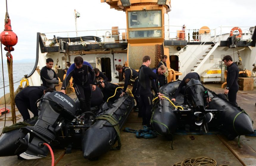Soldiers from the U.S. Army 10th Special Forces Group, out of Army Base Fort Carson, Colo., prepare their Zodiac rigid-hulled inflatable boats for deployment while aboard the Coast Guard Cutter Fir, a 225-foot Sea-going Buoy Tender during transit off the northern coast of Oregon, June 22, 2016. The cutter supplied equipment storage and deployment during a joint-agency operation. U.S. Coast Guard photo by Petty Officer Class Levi Read.