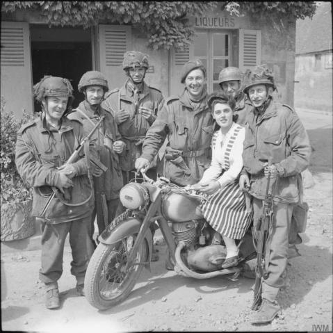 British glider troops pose with a local French girl on a captured German motorcycle, Normandy, 15th June 1944. note the MP40