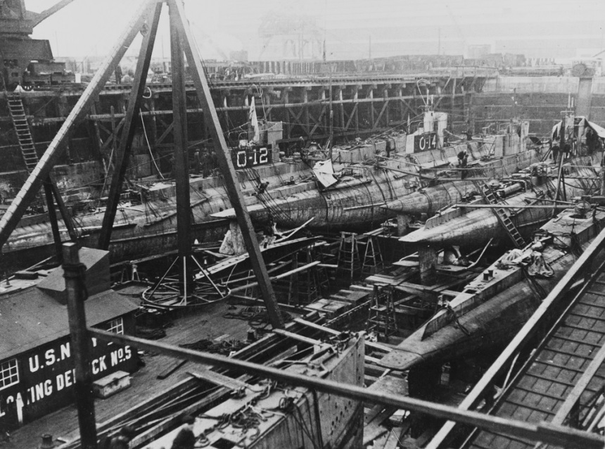 Submarines O-12, O-14, O-11, and others in dry-dock circa 1919 with floating Derrick No. 5 (YD-5). Description: Courtesy Philadelphia evening ledger. #: NH 42566