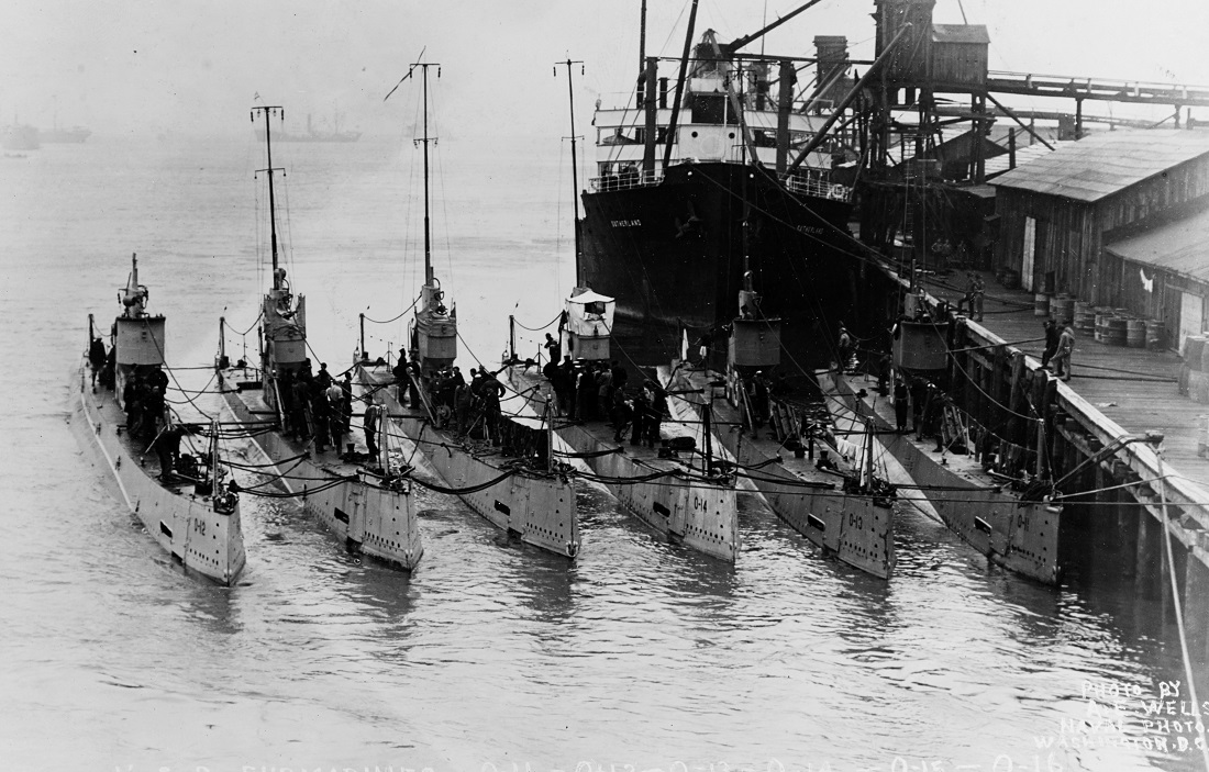 """O"" Class Submarines photographed in port by A.E. Wells of Washington, D.C., circa 1919, with S.S. SOTHERLAND in background. Subs are (l-r): O-12 (SS-73), O-15 (SS-76), O-16 (SS-77), O-14 (SS-75), O-13 (SS-74), O-11 (SS-72).#: NH 44558"