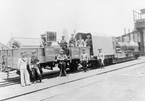 Royal Navy bluejackets of HMS Terrible pose by an armored train at Durban during the Boer War. Mounted on the flatbed carriage is an improvised signal lamp consisting of a searchlight and shutter mechanism, powered by a dynamo attached to the train. The officer to the right of the image is possibly Capt. Percy Scott RN. The tower of Durban Post Office can be seen in the background. IWM Q 115145
