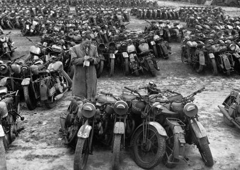These war-surplus motorcycles are bundled up in fives for disposal as scrap metal
