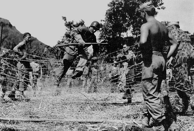 27th Infantry Division trains in Hawaii before embarking on the amphibious operation to seize Makin in the Gilbert Islands, Fall 1943. Soldier in one piece camouflage uniform is to the right.