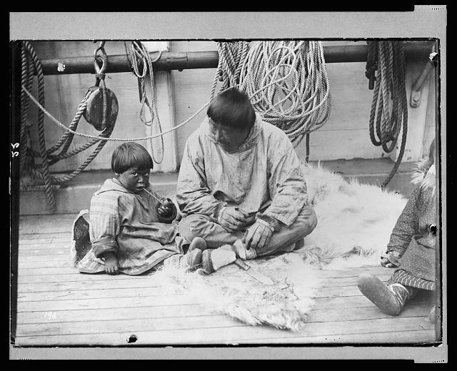 Photograph shows a Native American child and man sitting on the deck of a ship, the revenue cutter Bear during a relief voyage to rescue whalers off the Alaska coast in 1897. The man is showing the child how to smoke a pipe. By photographer Samuel Call. LOC.