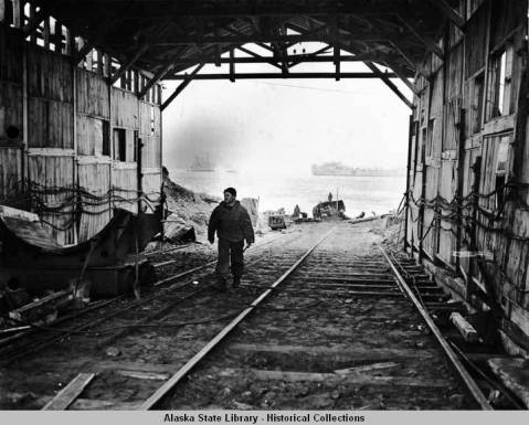 Inside view, looking seaward, of covered, Japanese submarine beaching railway, tracks leading to waterfront; a soldier passes large submarine handling cradles on left; warships are visible through opening.