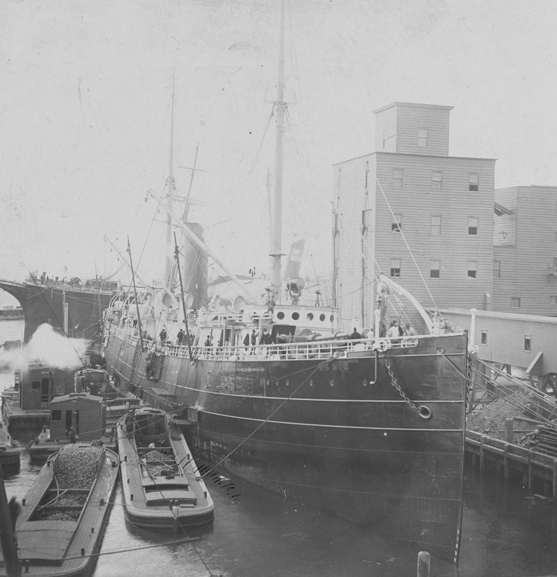 Probably shown fitting out for Brazilian Navy service in November 1893 at the Morgan Iron Works, New York City. Several barges are alongside. Nictheroy's single 15-inch dynamite gun is on the forecastle. A small quick-fire gun, probably one of her eight 6-pounder Hotchkiss weapons, is barely visible behind a shield on the weather deck aft. Six of the other 6-pounders were carried behind ports in the hull, along with four tubes for Howell torpedoes. Her former name, El Cid, has been painted out on the bow but the ship still wears the rest of her mercantile paint scheme. U.S. Naval History and Heritage Command Photograph. Catalog #: NH 105941