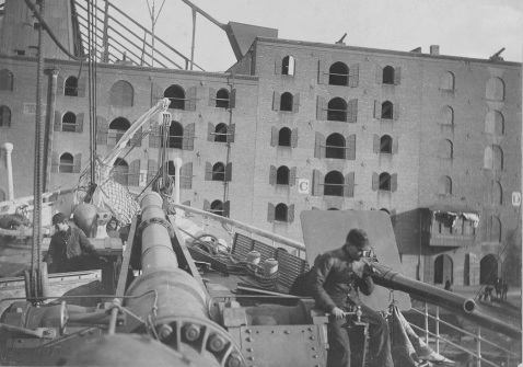 View on board, probably taken while fitting out for Brazilian Navy service in November 1893 at the Morgan Iron Works, New York City. Her single 15-inch dynamite gun on the forecastle (left center) was offset 3 feet to starboard of the centerline and was trainable right ahead and on both bows. The gun on the right may be one of the two 33-pounder (4-inch) Hotchkiss quick-fire guns that were listed as having been mounted forward on the bluff of the bow on each side. U.S. Naval History and Heritage Command Photograph. Catalog #: NH 105942