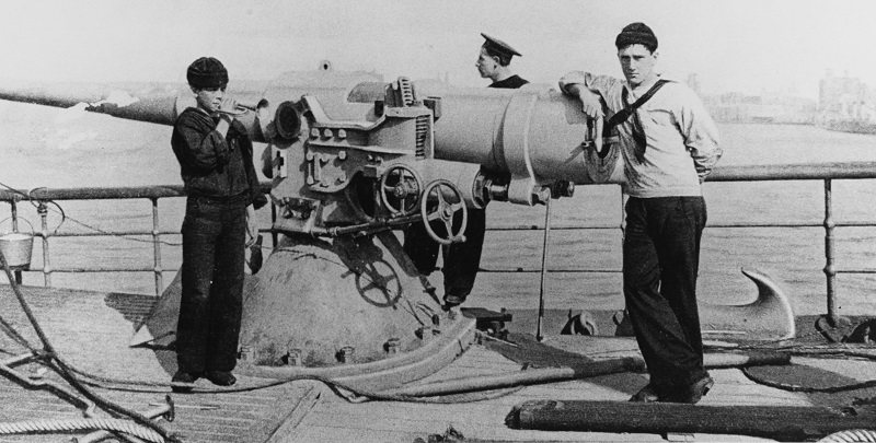 """A bugler sounding the call to breakfast in 1898. The gun appears to be a 4""""/40cal. At this time the ship carried four of these weapons plus two 5/40 guns. Courtesy of Commander Donald J. Robinson, USN (Medical Service Corps), 1975. U.S. Naval History and Heritage Command Photograph. Catalog #: NH 82990"""