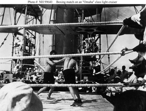 Boxing match held between the aircraft catapults of an Omaha (CL 4-13) class light cruiser, circa the mid-1920s. View looks forward, with the ship's after smokestack in the left center background. Donation of Ronald W. Compton, from the collection of his grandfather, Chief Machinist's Mate William C. Carlson, USN. U.S. Naval History and Heritage Command Photograph. Catalog #: NH 99640