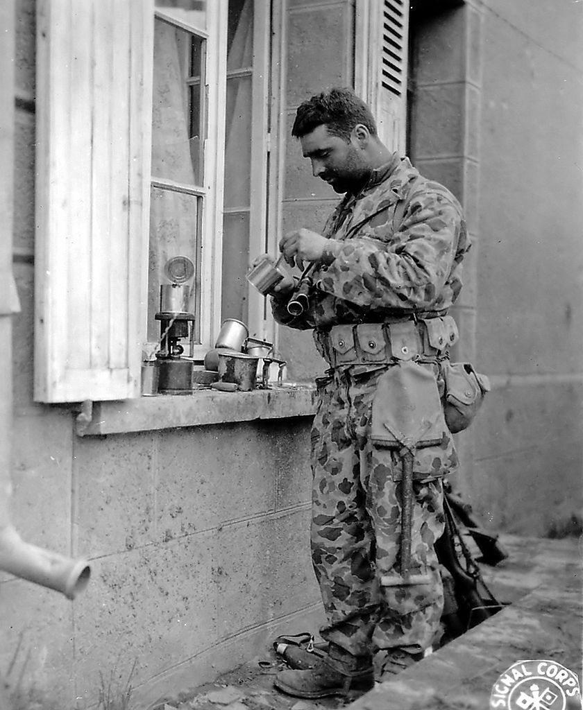 Private Joseph De Freitos of Yonkers (New York) of the 41st Armored Infantry Regiment, 2nd US Armored Division, heats his rations on a stove, taken at Pont-Brocard in late July 1944. There is nothing particularly strange about the way he is wearing his e-tool; this was fairly common when the M1928 haversack was not being used.