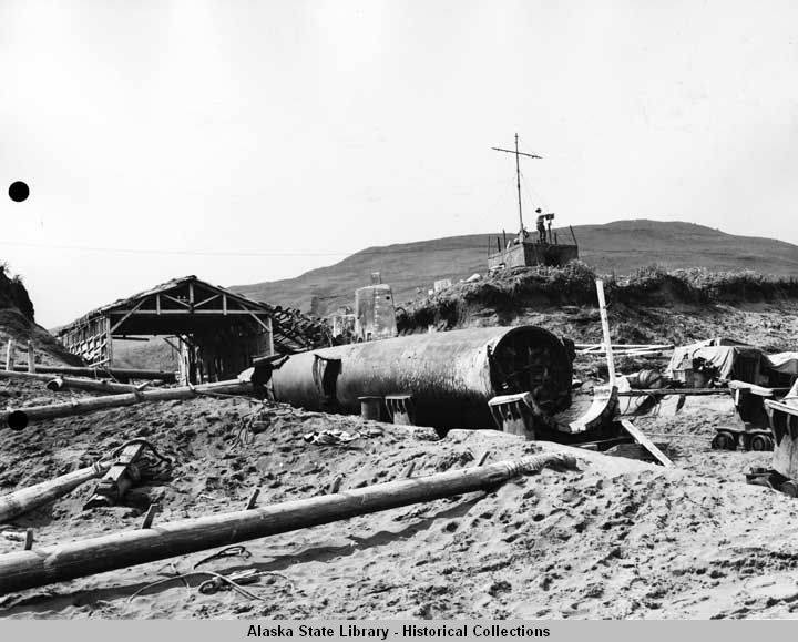 Submarines converted into scrap on Kiska Island, August 1943. Fleet Air Wing Four military personnel use torches to cut up submarines for scrap