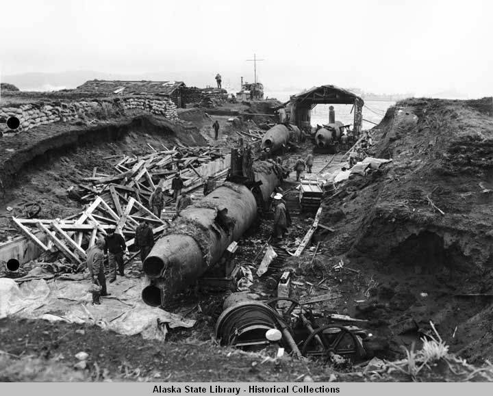 Two-person submarines, damaged by internal explosions, on Kiska, August 1943. Fleet Air Wing Four military personnel remove incapacitated submarines from marine railway track leading to waterfront; lumber is scattered along one side; sandbags line top of hillside; winches for hauling subs are at right. All of the submarines, as with other equipment left on the island by the Japanese, were captured in thoroughly disabled condition as to be expected.
