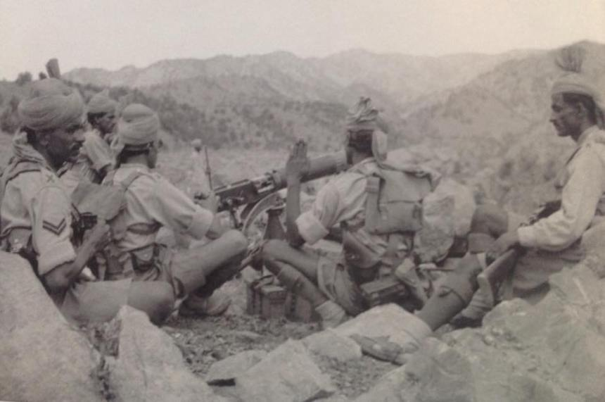 Vickers machine gun emplacement in a sangar, North West Frontier Province between the wars. The pouches on the back on the No. 2 (with his hand up) are for clinometer and the foresight bar deflector - seldom seen in the field. The headdress of British Indian troops was normally the khaki puggaree which varied by the soldier's religion--Muslims with a pointed kullah skullcap inside the puggaree and Sikhs with a more open version that allowed their uncut hair to remain in a bun atop their head, while most Hindu troops wore a simple turban. Photo via British Empire Uniforms 1939-45.