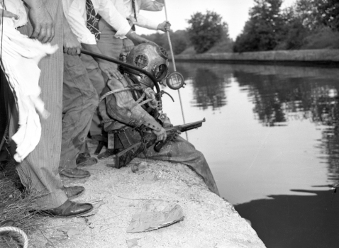 Official caption: Diver James P. Bodor, 23, finds a shotgun after he and officers dragged the bottom of the Cal-Sag canal at 107th Street and Archer Avenue looking for evidence in the Brink's Express robbery case on Aug. 5, 1949. Four men robbed the South Chicago Savings bank, located at 2959 E. 92nd Street, on June 25, 1949 and killed two Brink's Express guards, Joseph Den, 40, and Bruno Koziol, 36. The police had a confession from robber James Hoyland who fingered the other three bandits, Joseph Jakalski, Richard Tamborski, and David Edgerly. (Chicago Tribune historical photo)
