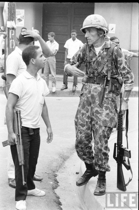 Italian merc Elio Capozzi (U.S. HBT camo and AR-10) speaks with a Dominican rebel with a Cristobol Carbine, 1965,