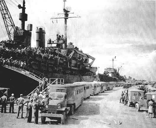 60 busses and ambulances await the arrival of the first 970 POWs returning to the U.S. from Japan aboard USS Ozark, Agana Guarm 13 Sept. 1945