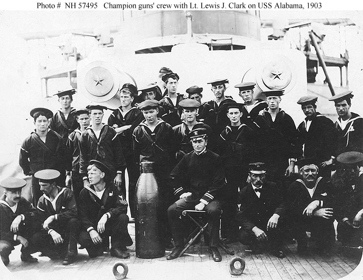 """Champion guns crew with Lieutenant Lewis J. Clark, 1903. They are posed with a 13-inch shell, on the foredeck in front of the ship's forward 13""""/35 gun turret.Photo # NH 57495."""